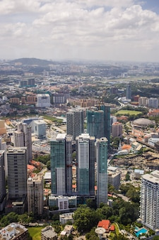 말레이시아 공원의 녹지에서 익사하는 고층 고층 빌딩이있는 쿠알라 룸푸르의 도시 전망
