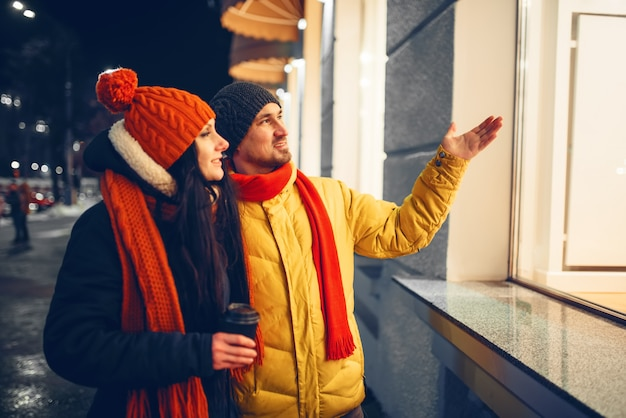 Urban winter evening, love couple looking on showcase. man and woman having romantic meeting on city street