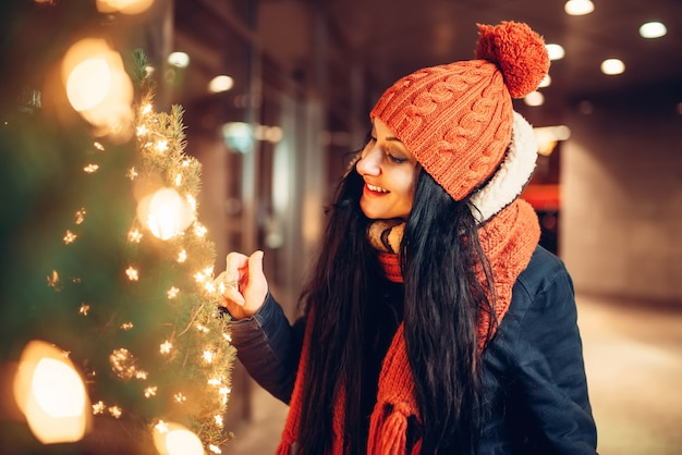 都会の冬の夜、歩くカップルが大好きです。イルミネーションとクリスマスツリーを探している女性