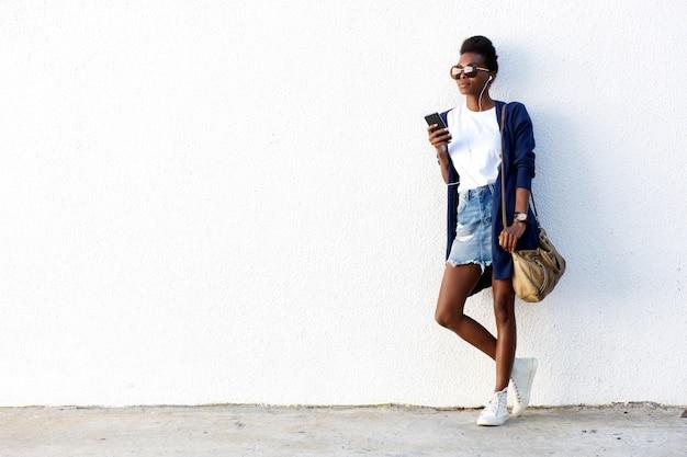 Urban woman listening to music on smart phone