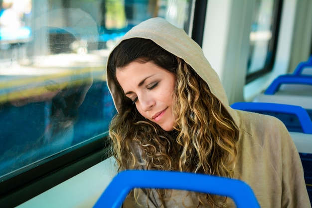 Urban woman sleeping in a train travel beside the window.