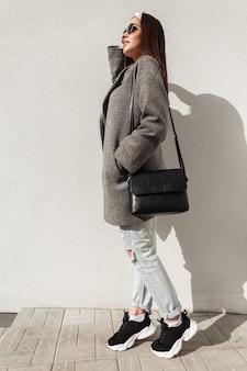선글라스에 핸드백이 달린 운동화에 청바지에 회색 코트를 입은 빈티지 반다나를 입은 도시 여성은 흰색 건물 근처에 서서 밝은 햇빛을 즐깁니다. 도시에서 평상복을 입은 아름다운 귀여운 소녀 모델.