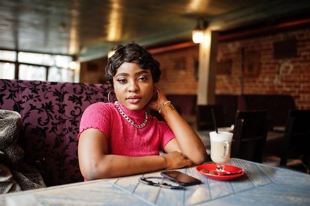 ピンクのトップの都会の若いアフリカ系アメリカ人女性がカフェに座ってラテコーヒーを飲みます。