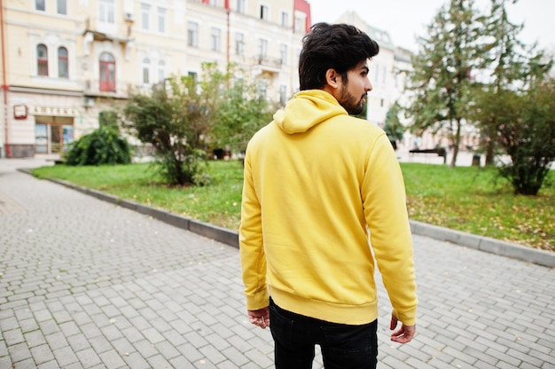 Urban young hipster indian man in a fashionable yellow sweatshirt. cool south asian guy wear hoodie walk on street.