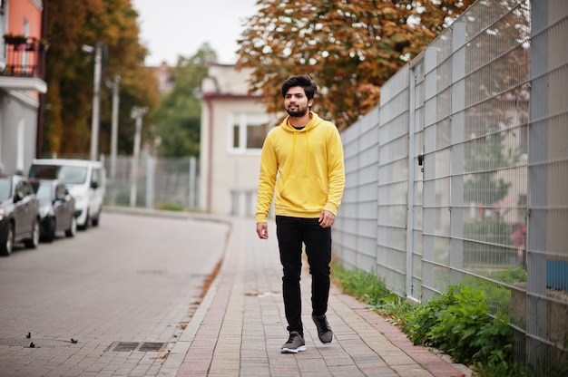Urban young hipster indian man in a fashionable yellow sweatshirt. cool south asian guy wear hoodie walking on fall street.
