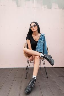 Городская молодая хипстерская женщина в черных кожаных сапогах в модной джинсовой одежде в стильных солнцезащитных очках позирует на соломенном стуле у розовой стены. модная девушка отдыхает на террасе летнего кафе.