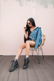 거리에 분홍색 벽 근처 짚의 자에 앉아 세련 된 가죽 블랙가 부츠에 트렌디 한 블루 데님 옷에 선글라스에 도시 젊은 hipster 여자. 야외에서 휴식하는 미국 소녀.