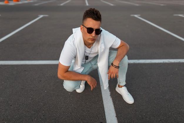 Городской молодой человек в солнечных очках, в модной летней одежде в кожаных белых модных кроссовках наслаждается отдыхом на асфальтовой дороге. модный парень со стильной прической сидит на открытой парковке.