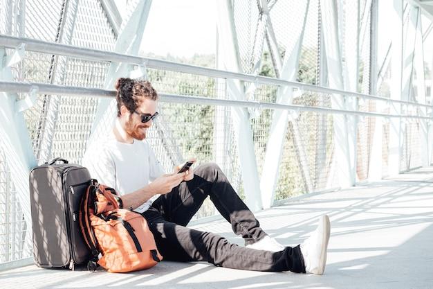 Городской молодой человек разговаривает по смартфону, путешествуя внутри в аэропорту. вскользь молодой бизнесмен нося пиджак костюма. красивая мужская модель. молодой человек с мобильным телефоном в аэропорту в ожидании