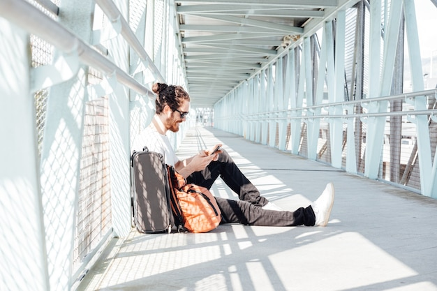 空港内を移動するスマートフォンで話している都会の若者。スーツのジャケットを着ているカジュアルな青年実業家。ハンサムな男性モデル。待っている間空港で携帯電話を持つ若い男
