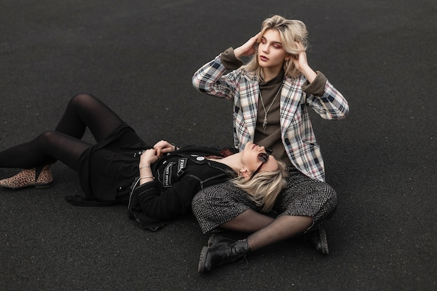 Urban young woman in black clothes in sunglasses lies on pavement next to blonde girlfriend in checkered blazer