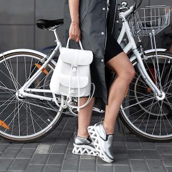 세련된 가죽 배낭이 달린 세련된 실버 스니커즈의 긴 재킷을 입은 도시 젊은 여성이 화이트 빈티지 자전거 근처의 도시 거리에 선다. 산책 유행 소녀. 확대.