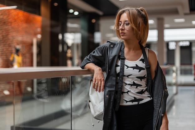 쇼핑 센터에 서있는 흰색 가죽 배낭과 치마에 여름 코트에 패턴으로 트렌디 한 티셔츠에 안경에 도시 젊은 여자. 매력적인 여자 실내입니다. 미국식