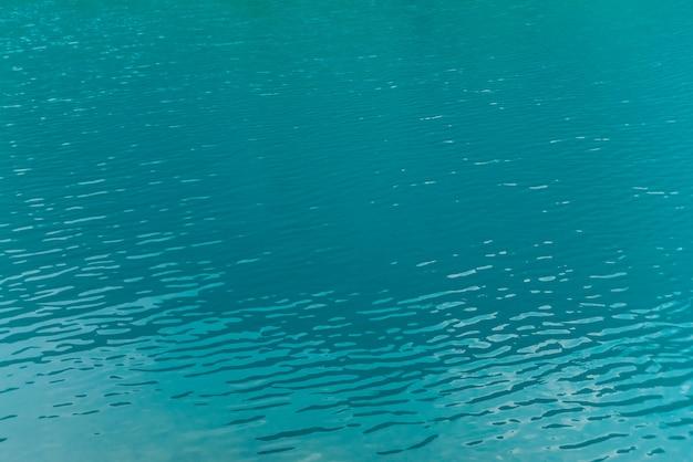山の湖の光沢のある質感紺ureの表面。晴れた日の澄んだ水の山の反射とミニマリスト。 copyspace。