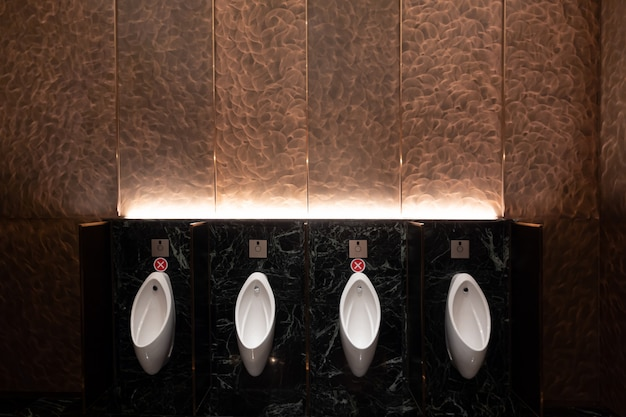 Urinal area with sign of social distancing with copper wall on the background