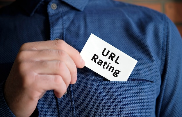 Url rating text on a white sign in the hand of a man in shirt
