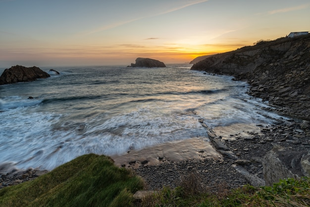 Восход солнца на пляже арния. urros de liencres. кантабрия. испания.