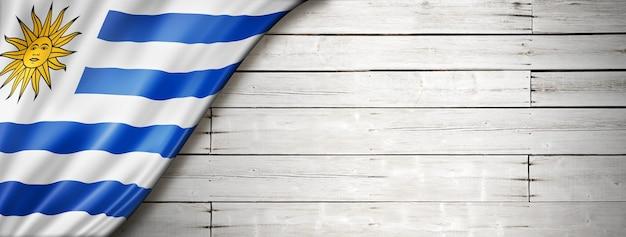 Флаг уругвая на старой белой стене. горизонтальный панорамный баннер.