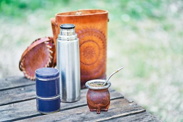 田舎の木製テーブルに電球、魔法瓶、バッグが付いた、革で裏打ちされたウルグアイのメイトキット