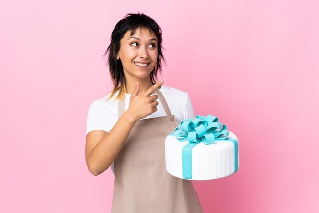 ウルグアイのペストリーシェフが人差し指で指している孤立したピンク色の背景の上に大きなケーキを置く素晴らしいアイデア