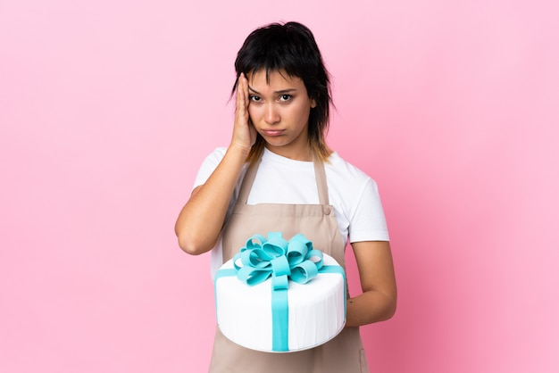 Uruguayan pastry chef holding a big cake over isolated pink unhappy and frustrated with something. negative facial expression