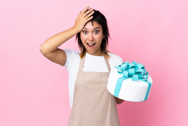 Uruguayan pastry chef holding a big cake over pink wall with surprise facial expression
