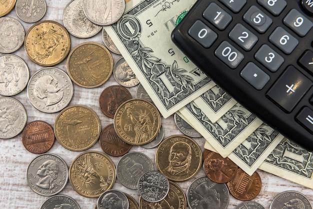 木製の机の上のコイン セントと米国 1 ドル札