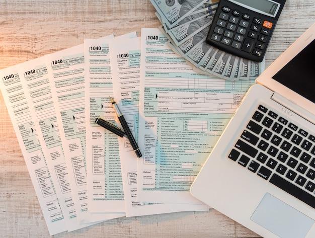 ペン、ドル、ノートパソコンをオフィスに置いた1040納税申告書。課税時間。会計の概念