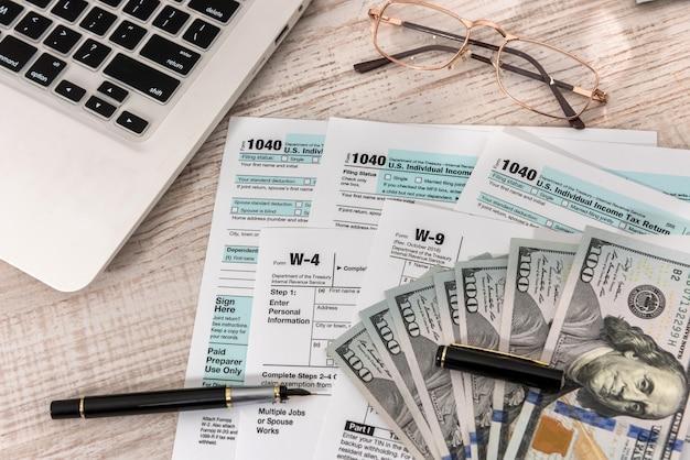 사무실에서 펜, 달러 및 노트북으로 미국 1040 세금 양식. 세금 시간. 회계 개념.