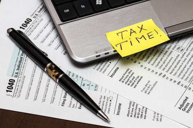 Us 1040 tax form with pen and laptop