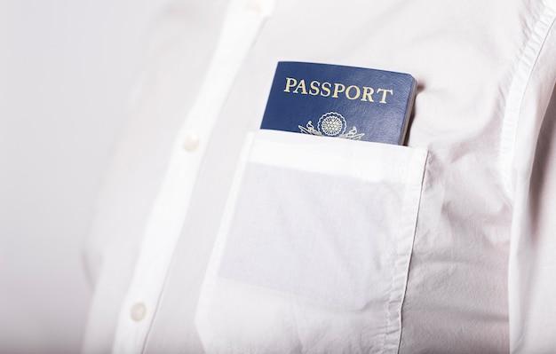 흰 셔츠의 주머니에 미국 미국 여권을 닫습니다. 이민 개념
