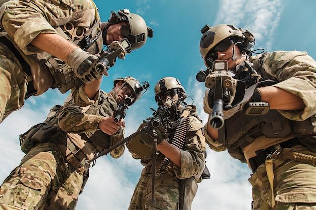 카메라를 억류하는 사람에게 무기를 가리키는 미 육군 레인저스. 낮은 각도 보기