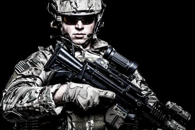 미군 병사, 해병대 기수, 전투복을 입은 특수부대 전투기, 헬멧과 안경, 라디오 헤드셋, 야간 투시경이 있는 무장 돌격 소총, 열상 상상, 검정색 배경의 광학 시력