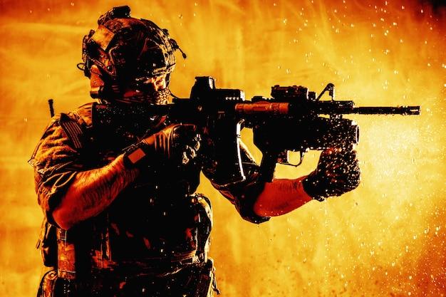 미 육군 특수부대 사수, 라디오 헤드셋이 있는 전투 헬멧을 쓴 현대적인 전투원, 얼굴을 숨기고, 소총을 조준하고, 적과 싸우고, 물방울이 있는 불 같은 배경에서 목표물을 쏘고