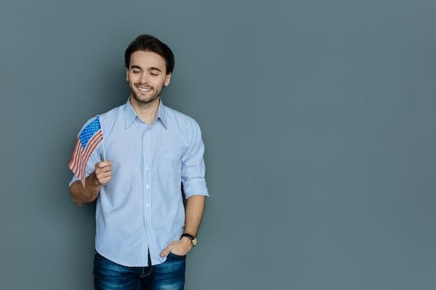 Гражданин сша. красивый веселый молодой человек улыбается и смотрит на флаг сша, чувствуя себя патриотом
