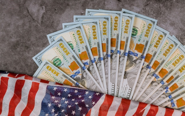 Us currency money of dollars on american flag