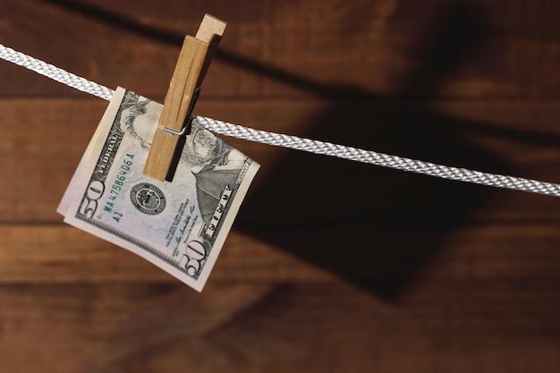 Банкнота доллара сша вешается на веревку с прищепкой. понятие об отмывании денег.