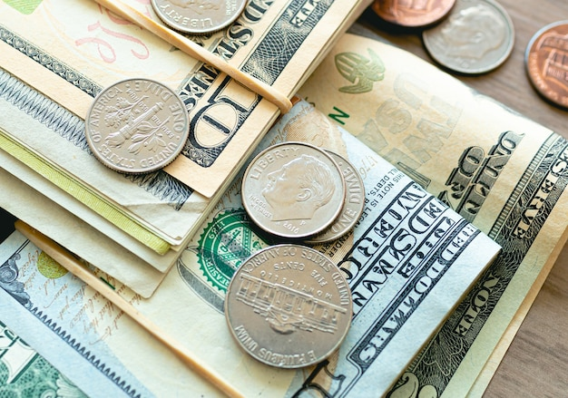 Us dollar banknotes and coins in closeup photography