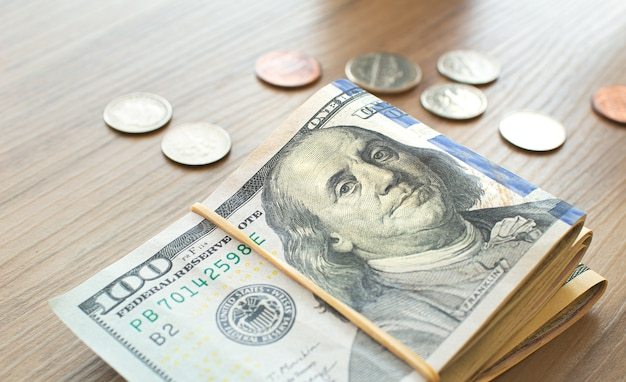 Us dollar banknotes and coins on wooden furniture in closeup photography