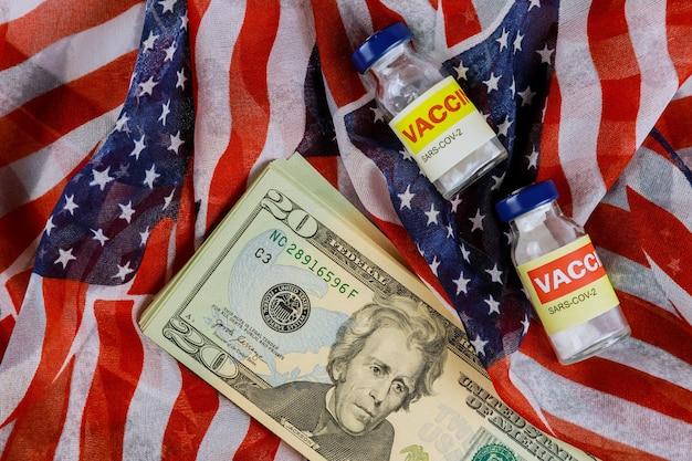 미국 국기와 싸우는 감염 sars-cov-2 코로나 바이러스 covid-19에 대한 병 및 주사기에 미국 백신의 미국 달러 지폐