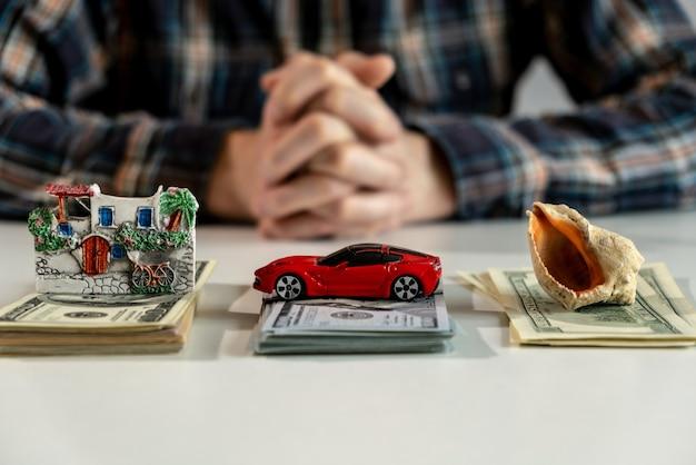 새로운 구매를 위한 미국 달러 banknotes.money. 자동차, 집, 여행을 위해 돈을 절약합니다. 저축 개념입니다. 작은 집, 자동차, 조개껍데기가 천 달러의 탁자 위에 놓여 있습니다. 고품질 사진