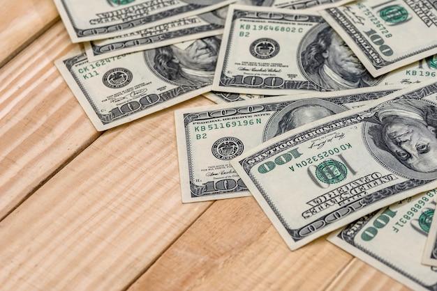 나무 책상에 미국 달러 지폐입니다.