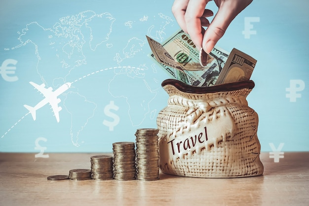 Us dollar bills in bag with coins stack on table, blur background with currency icons different countries, the silhouette of the plane and morning sun . concept of money saving on travel.