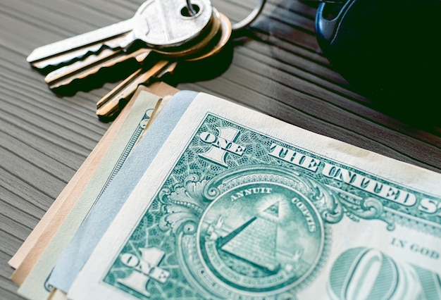 A us dollar bills in close up photo with keys in composition