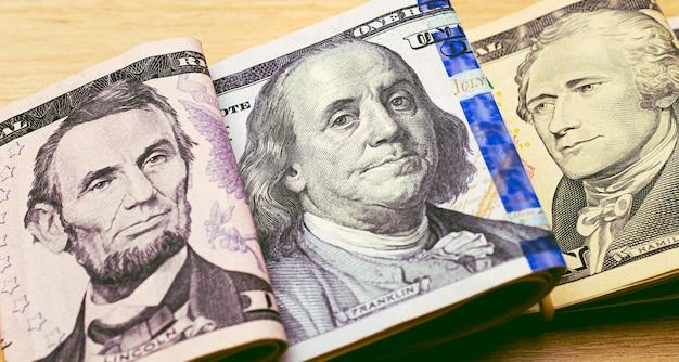 근접 촬영 사진에서 나무 테이블에 접힌 미국 달러 지폐