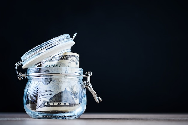 Us dollar bills in a glass jar with copy space. saving money and investment concept