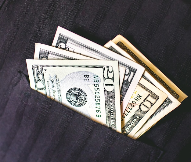 黒のシャツのポケットに米ドル紙幣