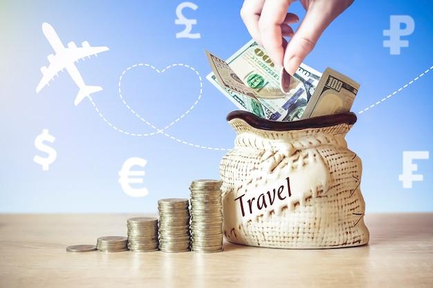 동전이 든 가방에 있는 미국 달러 지폐는 테이블 위에 쌓이고, 다른 나라의 통화 아이콘으로 배경을 흐리게 하고, 비행기와 아침 해의 실루엣을 흐리게 합니다. 개념 여행입니다.