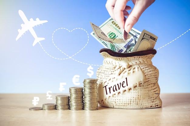 コインが入ったバッグの米ドル紙幣テーブルに積み重ね、さまざまな国の通貨アイコン、飛行機のシルエット、朝の太陽で背景をぼかします。旅行でお金を節約するという概念。