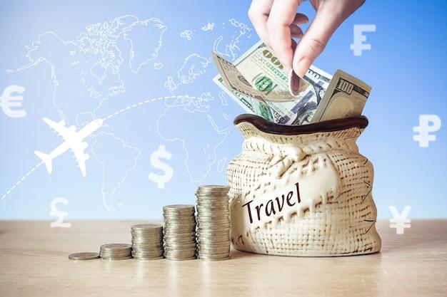 동전이 든 가방에 있는 미국 달러 지폐는 테이블 위에 쌓이고, 다른 나라의 통화 아이콘으로 배경을 흐리게 하고, 세계 지도, 비행기, 아침 해의 실루엣. 개념 여행입니다.